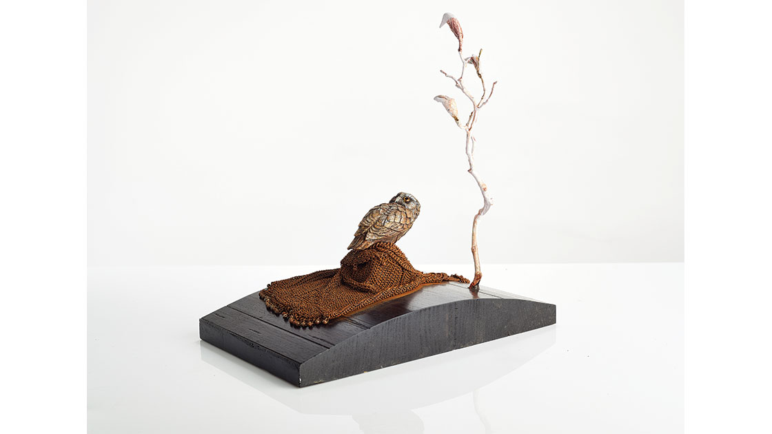 """""""Booty,""""  2020,  1830s metal mesh bag, found bird, tree form, pigmented gesso, acrylic, epoxy on timber base, 31 x 29 x 18 cm, courtesy the artist."""